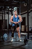 A Strong Bodybuilder With A Bandage On A Leg, Holding A Sports Hammer, Warming Up Before Training, I poster
