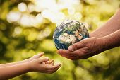 Close Up Of Senior Hands Giving Small Planet Earth To A Child Over Defocused Green Background With C poster