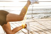 Close up of a sportswoman doing exercises with a rubber band at the beach poster