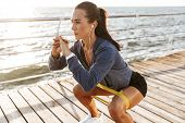 Concentrated sportswoman doing exercises with a rubber band at the beach poster