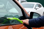 Man Cleaning His Orange Automobile With Green Mop. Washing Automobile Window. Horizontal View. poster
