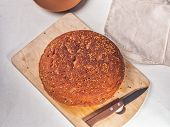 Homemade Homemade Bread Of Coarse Flour, Sprinkled With Flax Seeds Lies On The Kitchen Wooden Board. poster