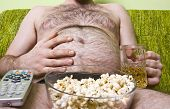 Fat man with glass of beer and popcorn