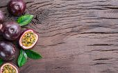 Passion fruits and its cross section with pulpy juice filled with seeds. Wooden background. poster