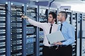 stock photo of racks  - group of young business people it engineer in network server room solving problems and give help and support - JPG