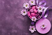 Purple And Pink Macaroons In A Gift Box On A Beautiful Purple Background Decorated With Flowers. Top poster