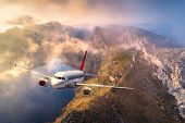 Airplane Is Flying Over Mountains And Low Clouds At Sunset In Summer. Landscape With Passenger Airpl poster