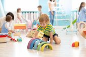 Kids Playing On Floor With Educational Toys. Toys For Preschool And Kindergarten. Children In Nurser poster