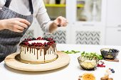Confectioner Decorates With Berries A Biscuit Cake With White Cream And Chocolate. Cake Stands On A  poster