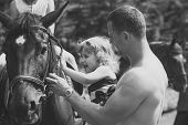 Child With Muscular Macho Smile To Animal. Girl With Man Pet Horse On Sunny Day. Equine Therapy, Rec poster