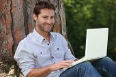 stock photo of breather  - Man on laptop outside - JPG