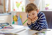 Portrait Of Cute Happy School Kid Boy At Home Making Homework. Little Child Writing With Colorful Pe poster
