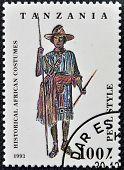 TANZANIA - CIRCA 1993: Een stempel gedrukt in Tanzania gewijd aan historische Afrikaanse kostuums toont pe