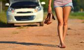 A woman hold her shoes and walk  after her car broke down