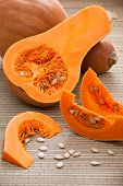 Ripe Orange Pumpkins, Sliced Segments And Seeds On Woven Surface