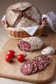 Slices Salami On Board, Cherry Tomatoes Bread In Breadbasket