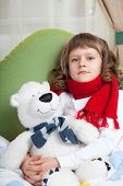 Little Sick Girl With Scarf Embraces Toy Bear In Bed Close-up