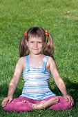 Smiling Child Sit And Meditate In Asana On Green Grass