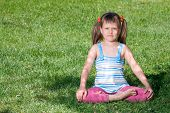 Little Girl Sits In The Shade In Asana On Grass