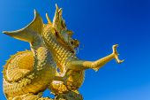 stock photo of divine mercy  - A golden dragon sculpture with blue sky in Phuket - JPG