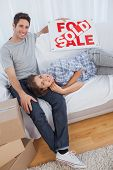 Man in his new house holding a sign with sold written on it with his wife lying on him