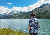 stock photo of engadine  - boy on the shore of a mountain lake - JPG