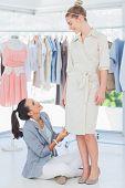 Mode-Designer sitzt neben einem Modell und Kleid anpassen