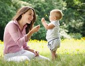 foto of infant  - Portrait of a mother giving child flower in the park - JPG