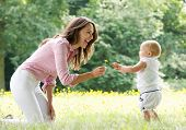 Happy Mother Teaching Baby To Walk In The Park