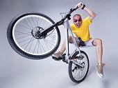 picture of dirt-bike  - crazy boy on a dirt jump bike on grey background  - JPG