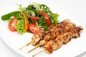 stock photo of sate  - Delicious chicken satay skewers with fresh green salad.