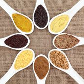 Mustard selection of powder, seed, french, dijon, english and wholegrain in white porcelain spoons over hessian background.