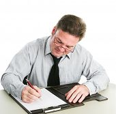 Businessman looking down and taking notes on a legal pad.  White background.