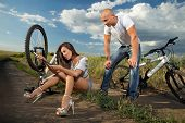 Bicycle has flat tyre and woman pumping it up