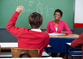 Rear view of schoolboy raising hand with female teacher in background at classroom