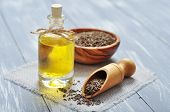 picture of cumin  - cumin oil in a glass bottle with cumin seeds on wooden background - JPG
