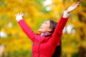 Autumn / fall woman happy in free freedom pose with arms raised up towards the sky with smiling chee