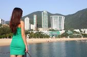 Hong Kong tourist woman at Repulse Bay beach. Beautiful Asian woman in summer dress enjoying view. H