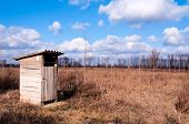 stock photo of outhouses  - Small wooden toilet in rural aerial with clouds - JPG