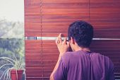 stock photo of peeping tom  - Young Man Peeping Out Through Venetian Blinds - JPG