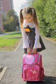 The schoolgirl with a heavy satchel