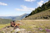picture of knapsack  - Hiking Boots and Knapsack Near a Road into the Far Mountains