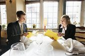 Young business couple with menus at restaurant table