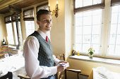 Side view of waiter with notepad smiling in restaurant