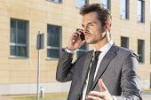Young businessman conversing on cell phone against office building