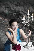 Girl Sits Near Table With Red Roses And Keeps Candlestick With Three Burning Candles In A Forest