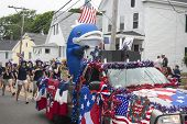 Person in a whale costume rides in the back of a truck in the Wellfleet 4th of July Parade in Wellfl