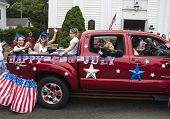 People ride in the back of a truck in the Wellfleet 4th of July Parade in Wellfleet, Massachusetts.