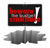 pic of waste reduction  - Beware the Budget Sinkhole words sign hole - JPG