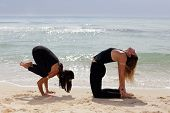 Women performing yoga on the beach